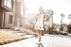 Beautiful dark-haired girl wearing little crown walking near her house. Walk near house. Beautiful dark-haired girl wearing little crown jumping high while stock photos