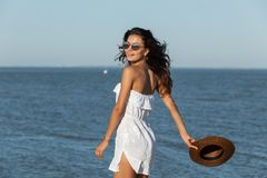 Beautiful dark-haired girl in white dress and sunglasses hold hat in hand and walk near the sea on a sunny day. stock image