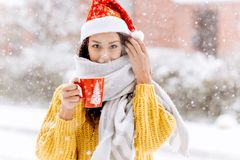 Beautiful dark-haired girl in a yellow sweater, a white scarf in Santa Claus hat is standing with a red mug on a snowy. Street on a winter day stock images