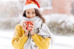 Beautiful dark-haired girl in a yellow sweater, a white scarf in Santa Claus hat is standing with a red mug on a snowy. Street on a winter day stock photos