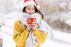 Beautiful dark-haired girl in a yellow sweater, a white scarf in Santa Claus hat is standing with a red mug on a snowy. Street on a winter day royalty free stock photos