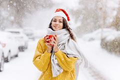 Beautiful dark-haired girl in a yellow sweater, a white scarf in Santa Claus hat is standing with a red mug on a snowy. Street on a winter day stock image