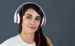 Beautiful dark haired smiling woman wearing headphones Stock Photos