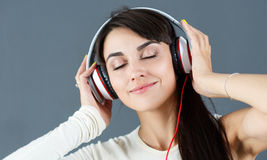 Beautiful dark haired smiling woman wearing headphones Royalty Free Stock Images