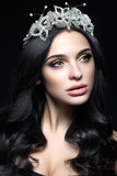 Beautiful dark-haired woman with a crown of precious stones, curls and evening makeup. Beauty face. Picture taken in the studio on a black background royalty free stock photo