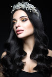 Beautiful dark-haired woman with a crown of precious stones, curls and evening makeup. Beauty face. Royalty Free Stock Images