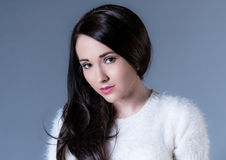Beautiful dark haired woman in white sweater. On blue background stock image