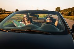 Beautiful dark-haired young women in sunglasses are sitting in a black cabriolet on a sunny day. One of them keeps map royalty free stock photography