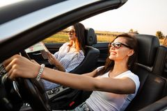 Beautiful dark-haired young women in sunglasses are sitting in a black convertible car on a sunny day. One of them keeps stock images
