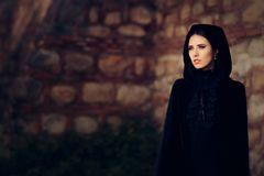 Beautiful Dark Princess in Black Hooded Cape. Magical fantasy portrait of a medieval witch royalty free stock photography