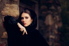 Beautiful Dark Princess in Black Hooded Cape. Magical fantasy portrait of a medieval witch stock photography