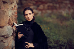 Beautiful Dark Princess Reading a Book. Portrait of gothic queen outside with storybook Stock Image