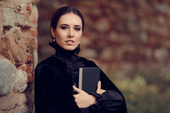 Beautiful Dark Princess Reading a Book. Portrait of gothic queen outside with storybook Royalty Free Stock Photography