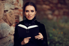 Beautiful Dark Princess Reading a Book. Portrait of gothic queen outside with storybook Stock Photos