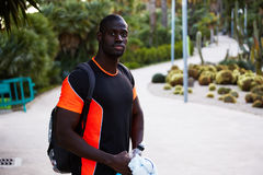A beautiful dark-skinned athlete goes for a jog in the park with a backpack. African-american sportsman finish to training looking to the camera standing in the Stock Photo