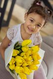 Beautiful dark-skinned girl going to present flowers. For my mom. Charming international child expressing positivity while posing on camera royalty free stock photo