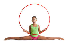 A beautiful dark-skinned girl performs a cross-split. A girl holding a hoop. Stock Image