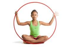 A beautiful dark-skinned girl sitting on the floor cross-legged. Girl holds the hoop. Royalty Free Stock Images