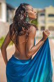 Beautiful dark-skinned latin girl with nude back. Photo shoot of a beautiful dark-skinned latina on the background of nature, in the amphitheatre, on the Royalty Free Stock Photography