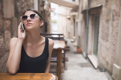 Beautiful dark tan European woman talking on the phone with friend gossiping. Business woman talking phone in the cafe in old town. Small charismatic street royalty free stock image