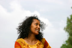 Beautiful dark woman smiling. Against blue sky Royalty Free Stock Photography