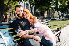 Beautiful dating couple hugging on a bench. At park Stock Photography