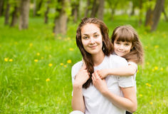 Beautiful daughter embraces young mother in park Royalty Free Stock Photography