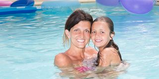 Daughter with pretty single mother in home private pool stock images
