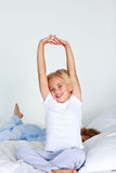 Beautiful daughter stretching after sleeping Royalty Free Stock Image