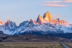 Beautiful dawn golden orange light of sun rise over the Fitz Roy and Cerro Torre peak snow mountain in the morning beside the. Route 40 road from El Calafate to stock photography
