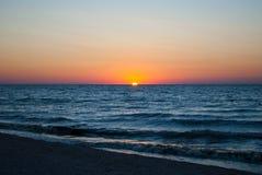 Beautiful dawn, red sun, purple pink sky, clear sky, sunrise over the sea, blue sea, waves Stock Photo