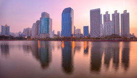 Beautiful dawn scenery of lakeside skyscrapers reflecting on smooth lake water in Benjakiti Park Royalty Free Stock Photography