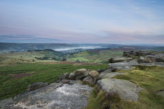 Beautiful dawn sunrise landscape image from Higger Tor towards H. Stunning dawn sunrise landscape image from Higger Tor towards Hope Valley layered in fog in Royalty Free Stock Photography