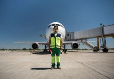 Aviation marshaller posing at airport and holding signal wands stock photo