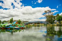 Beautiful day of an artificial lake located in the midle of a park, with some boats of animals in the water with the. Reflection in the city of Cayambe, Ecuador royalty free stock photo