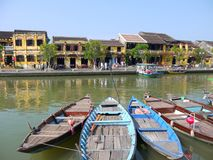 Beautiful day in Hoi An ancient town with view of traditional boats, yellow houses and tourists stock photo