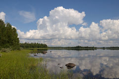 Beautiful day in Karelia region. The beautiful picture of Karelian forest at the edge of a lake, and some huge boulder in this lake stock photos