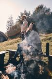 Beautiful day. Modern young couple having morning coffee while s. Pending time by the campfire in mountains Stock Photos