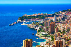 A beautiful day in Monte Carlo. This image shows a bird`s-eye view of the Larvotto beach, the Casino area, the port, the Rocher, and the Mediterranean sea Stock Image
