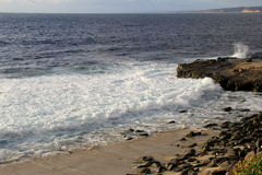 Beautiful day, with waves crashing against the rocky shoreline Stock Photos