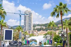 Beautiful daylight view to city buildings and peoples preparing. Scene. Big green mountains and bright blue sky on background. Monaco, France Royalty Free Stock Images