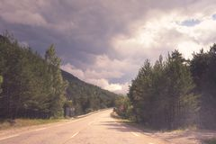 Beautiful daytime landscape with mountain road and amazing cloudy sky. Beautiful day time landscape with mountain road and amazing cloudy sky. Pass through the royalty free stock images