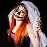 Beautiful dead bride with terrible mask painted on her face. Halloween and creative make-up. royalty free stock images