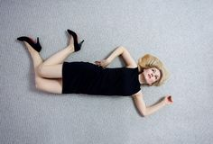 Beautiful dead woman in black dress lying on the floor. royalty free stock photos