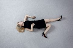 Beautiful dead woman in black dress lying on the floor. royalty free stock image