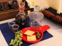 A beautiful decanter, with a red wine to wash down th crackers, grapes and olives. stock image
