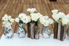 Beautiful decor at the wedding. Arrangement of white flowers, in vases reeds. On the background wooden floor. Royalty Free Stock Photo