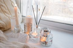 Beautiful decor of white lighted candles in glass candlesticks stand on windowsill, relax place in house, concept of winter cozy. Weekend or holiday royalty free stock photo