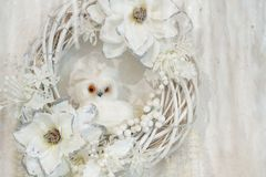 Beautiful decor, white wreath with flowers and little white owl.  stock photos