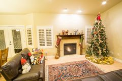 Beautiful Christmas tree and fireplace with cat relaxing on couch. Beautiful decorated Christmas tree and fireplace a night with glowing lights and cat resting Royalty Free Stock Images